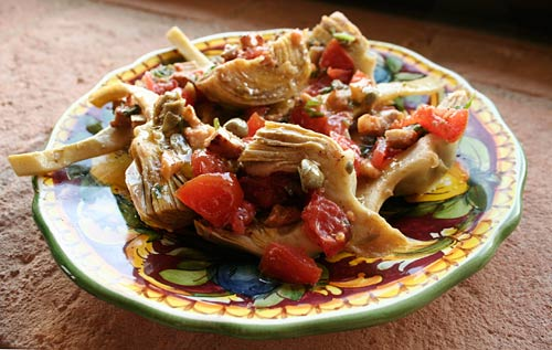 A warm pancetta dressing is used to top tender artichokes in this flavorful dish.
