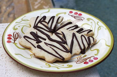 A buttery shortbread type cookie finished off with a drizzle of chocolate.
