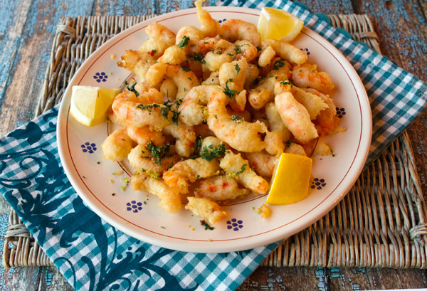 Barely fried shrimp are topped with a zesty lemon and parsley topping.