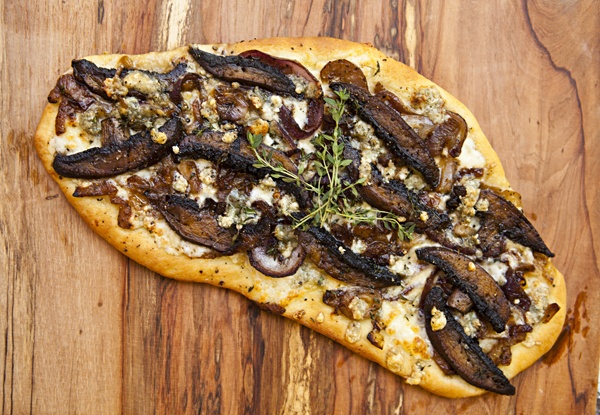 A crispy brown flatbread topped with sweet caramelized onions, earthy mushrooms, and salty Gorgonzola crumbles.