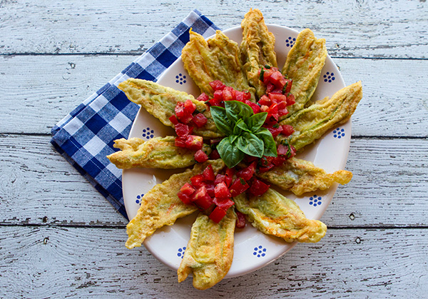 Simple, cheese stuffed fried zucchini flowers topped with a fresh, ripe tomato relish.