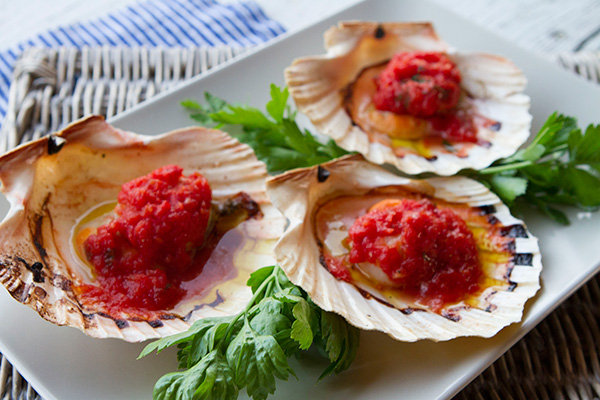 Scallops are topped with a fresh tomato sauce and a drizzle of olive oil inspired by our trip to Burano.