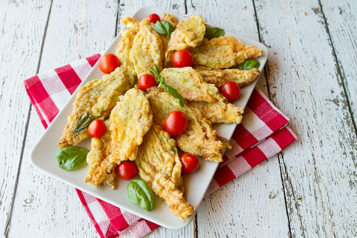 Zucchini flowers are stuffed with a combination of creamy mozzarella and ripe chopped tomatoes before frying.