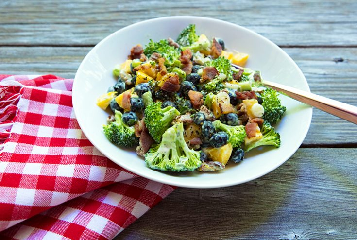 A unique crunchy salad pairing sweet blueberries and mango with raw broccoli.