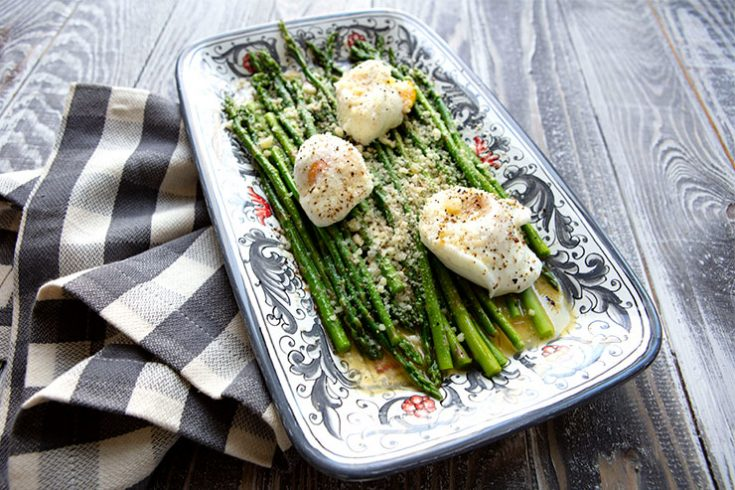 A simple dish of tender crisp asparagus topped with a fried egg and grated Parmesan cheese.