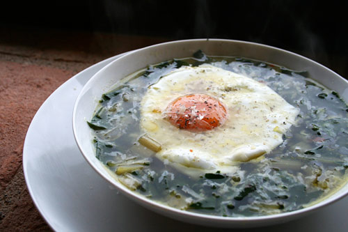 A simple country peasant soup made of fresh garden greens and topped with a fried egg.