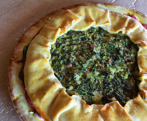 A tasty, savory tart filled with greens, pancetta, and onions.