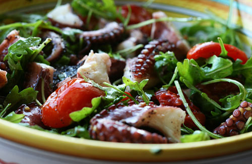 Tender octopus is served on bitter greens with sweet cherry tomatoes.