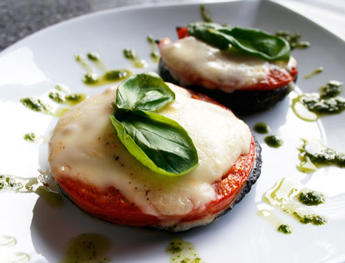 Mozzarella and tomato stuffed mushroom caps.
