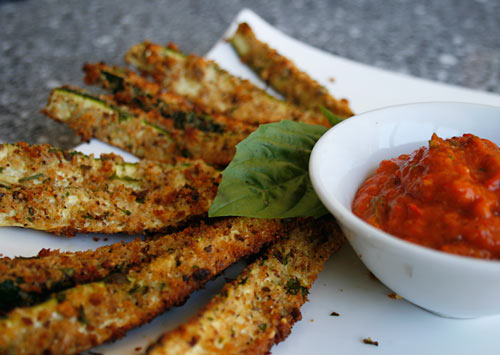 Crispy, golden brown breaded zucchini sticks are served with a spicy sauce.
