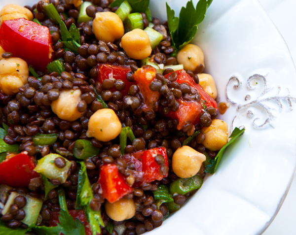 A healthy combination of fresh vegetables, black lentils, and chickpeas create a delicious hearty salad.
