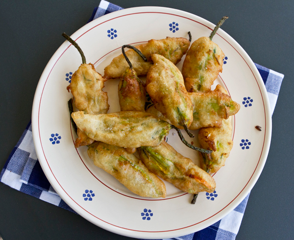 Crisp beer battered zucchini flowers are stuffed with mozzarella and anchovies.