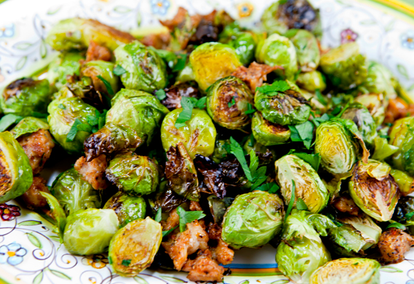 Roasting sprouts with sausage crumbles creates a hearty side dish or appetizer.