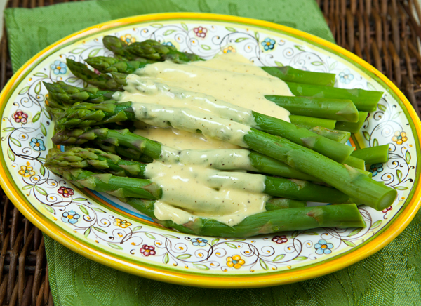 Tender spears of asparagus are topped with creamy, rich Hollandaise sauce in a side dish that would be perfect for spring entertaining.