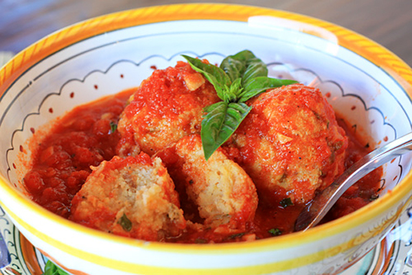 "Stale bread, grated cheese, and a few eggs are combined to create tender ""meatballs"" cooked in sauce."