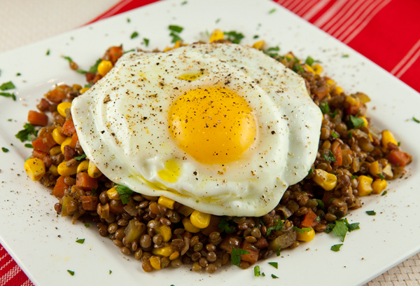 Tender braised lentils mixed with veggies are topped with a fried egg for a meatless entree.