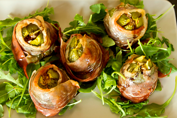 Fresh figs are stuffed with goat cheese and then wrapped in prosciutto before being baked in this easy summer recipe.