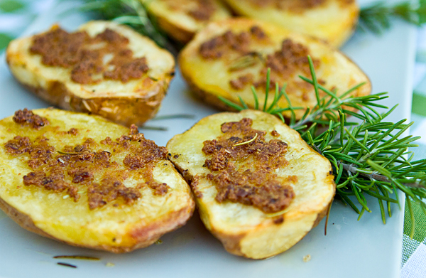 Crispy golden potatoes cooked on olive oil are topped with roasted garlic.