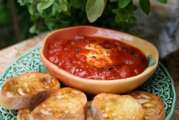 The easiest appetizer recipe for warm creamy goat cheese surrounded by tomato sauce.
