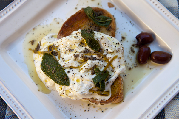 Creamy burrata cheese is served on toasted crusty bread slices and is then drizzled with a vibrant dressing.