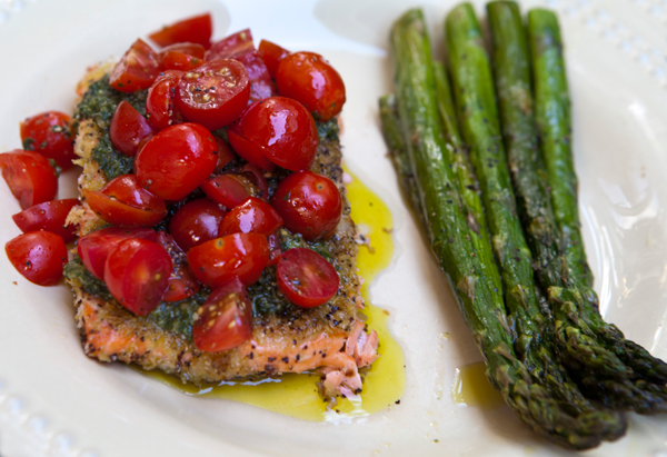 Wild salmon is topped with fresh tomatoes and pesto in this zesty dish.
