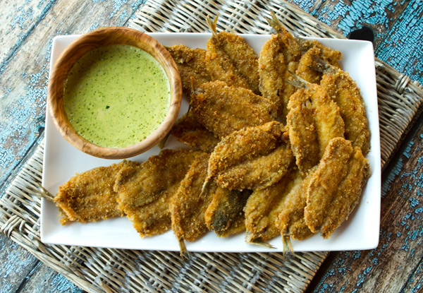Quick fried breaded sardines are served with a zesty parsley sauce.