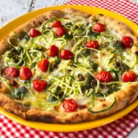 Pizza With Zucchini Spirals, Pistachio Pesto, Cherry Tomatoes, & Taleggio Cheese