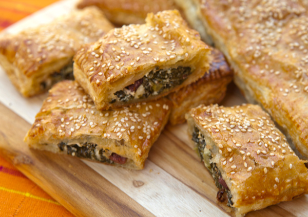 Tender kale and cheese filled golden puff pastry bundles are cut into slices for serving.