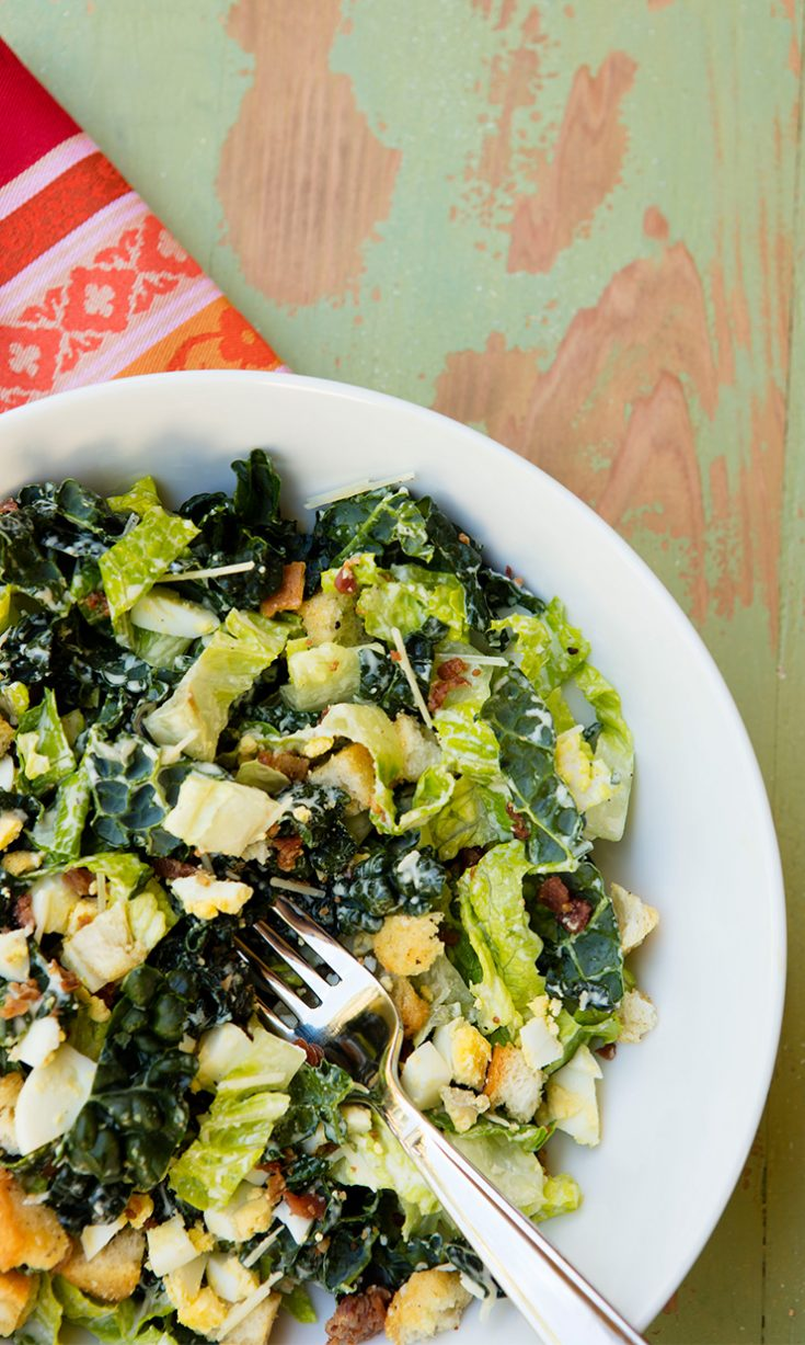The addition of kale to a Caesar salad along with a lightened up dressing creates a much healthier salad.