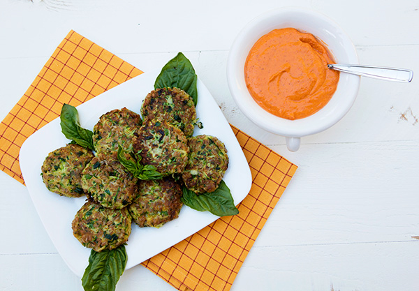 Tender vegetable and grain cakes served with a vibrant pepper sauce.