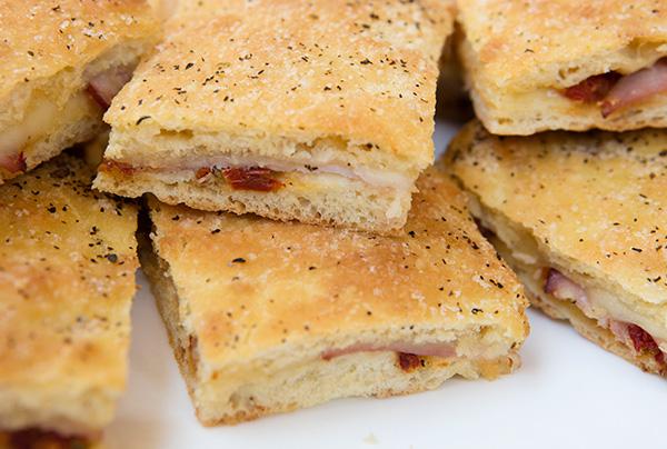 Focaccia tuffed with ham, provolone cheese, and a vibrant sun-dried tomato pesto spread.