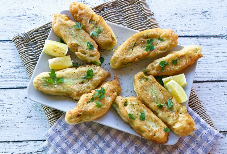 Tender blossoms stuffed with creamy cheese studded with fresh herbs are pan-fried until golden brown.