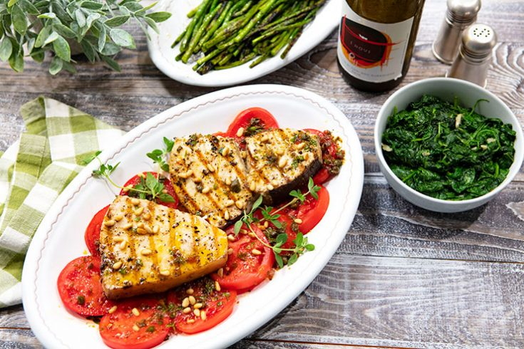 Grilled swordfish steaks served on a bed with ripe, summer tomatoes with a dressing of fresh oregano and capers.