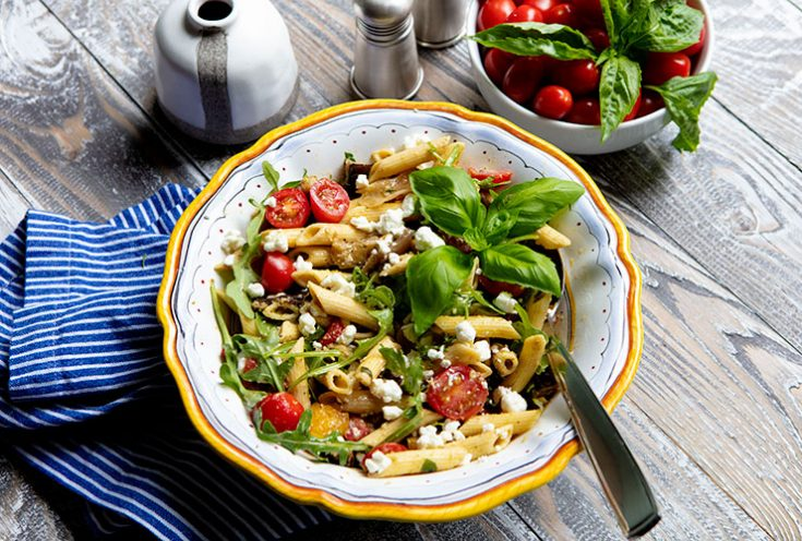 A summer inspired pasta salad chock full of grilled veggies and dressed with a pesto flavored vinaigrette.