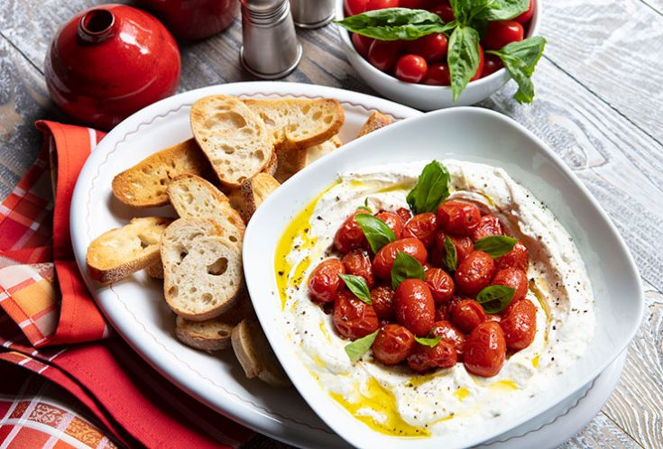 Creamy smooth whipped ricotta cheese seasoned with herbs is topped with slow roasted tomatoes and served with grilled bread slices.