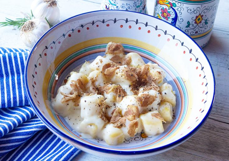 Light, pillowy potato gnocchi is topped with a truffle flavored cheese sauce in this Umbrian recipe.