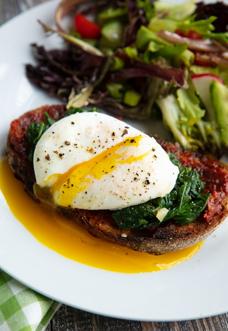 Spicy nduja, tender sauteed greens, and a perfectly poached egg are served on toasted slices of rusty bread.
