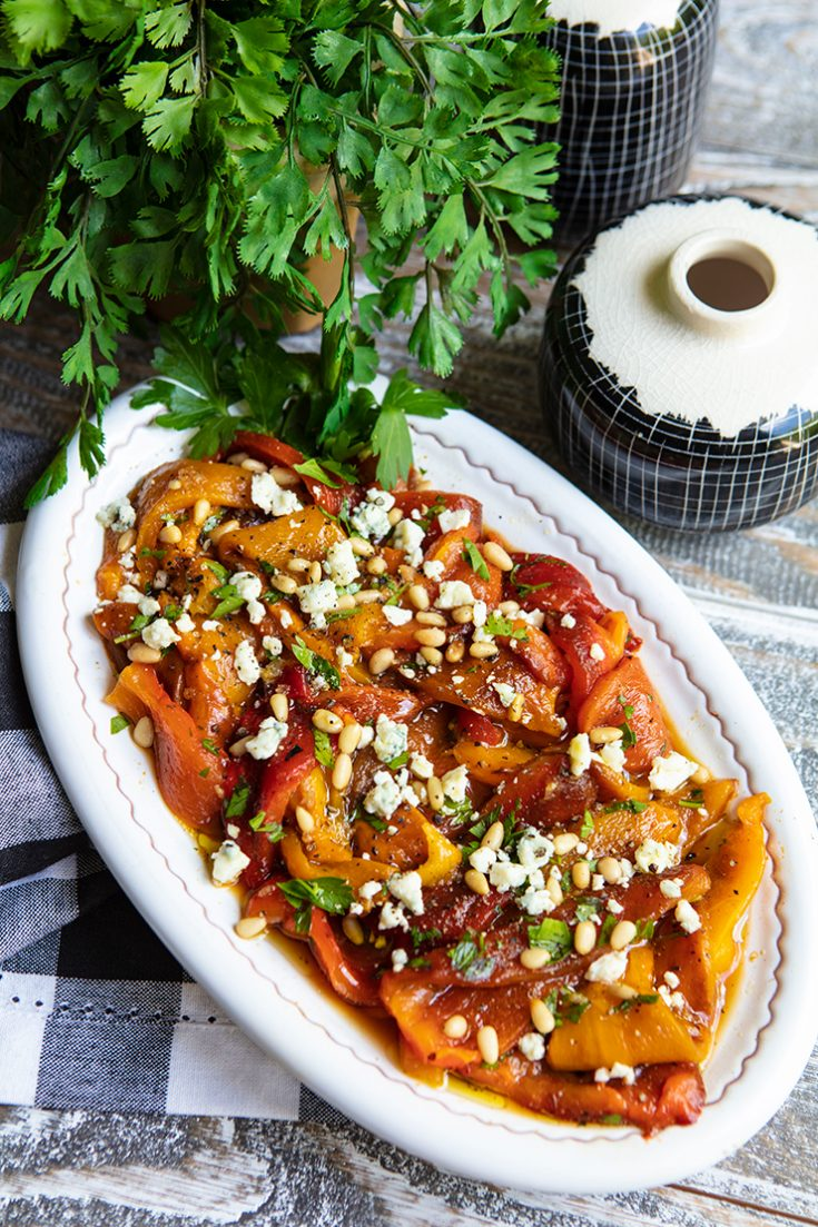 Grilled peppers are topped with cheese crumbles and pine nuts in this easy summer side dish.