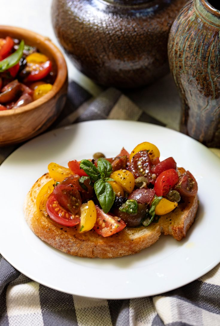 Adding capers, olives, and anchovy paste to chopped tomatoes creates the perfect topping for grilled bread.